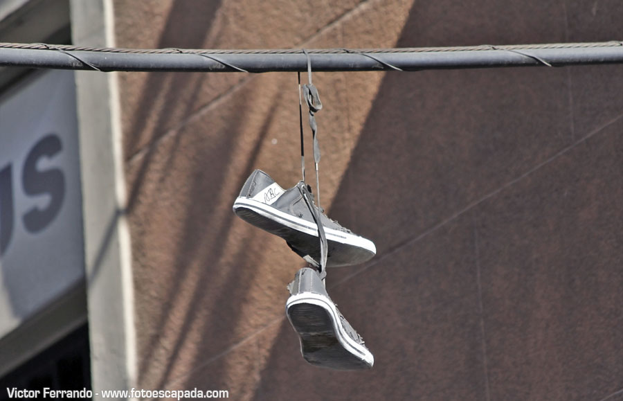 Shoefiti arte urbano en forma de zapatillas colgadas de un cable en Madrid