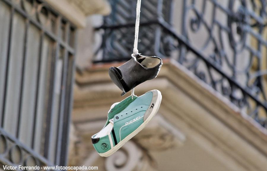 Shoeffiti arte urbano en forma de zapatillas colgadas de un cable en Madrid